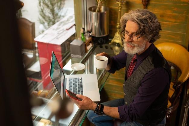 Komunikowanie się z przyjaciółmi. uśmiechnięty przystojny mężczyzna siedzi w kawiarni z filiżanką kawy i smartfonem w dłoniach, odpowiadając na jego wiadomości.