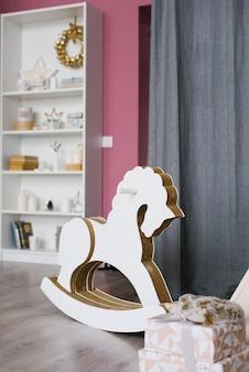 Koń na biegunach w pokoju dziecięcym urządzony na boże narodzenie