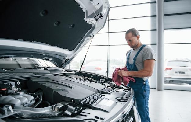 Koncentracja w pracy. mężczyzna w niebieskim mundurze pracuje z zepsutym samochodem. dokonywanie napraw