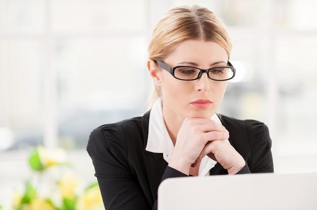 Koncentracja w pracy. poważna dojrzała kobieta w stroju formalnym trzymająca się za ręce na brodzie i patrząca na laptopa siedząc w miejscu pracy