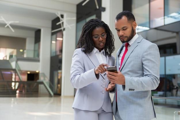 Koncentrujący się biznesowi koledzy z smartphone