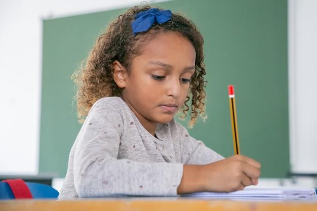 Koncentruje się african american szkoły podstawowej dziewczyna siedzi przy biurku i pisze ołówkiem
