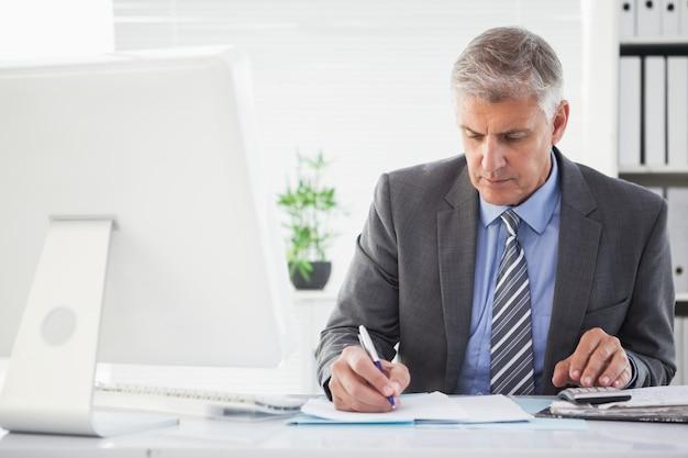 Koncentruje się biznesmen coś pisze w dół