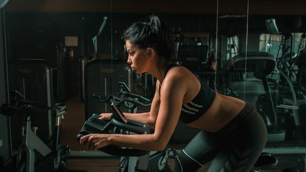 Koncentruje się całkiem młoda sportsmenka ćwiczeń na rowerze w siłowni