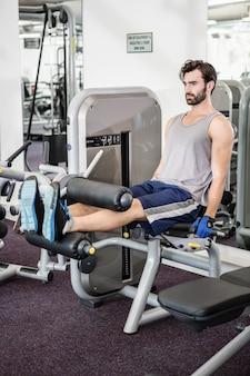 Koncentruje się człowiek za pomocą wagi maszyny do nóg na siłowni