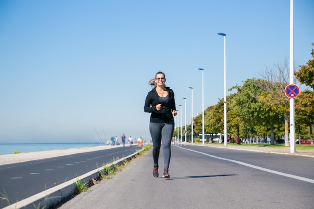 Koncentruje się dojrzała kobieta w strojach fitness, biegając wzdłuż brzegu rzeki na zewnątrz, ciesząc się poranny bieg. widok z przodu, na całej długości. koncepcja aktywnego stylu życia