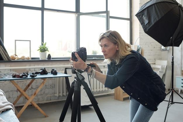 Koncentruje się dojrzała kobieta z okularami na głowie, pracując z aparatem fotograficznym w nowoczesnym studio fotograficznym