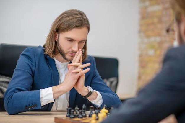 Koncentruje się inteligentny młody człowiek w niebieskiej kurtce myśli szachy ruch i plecy drugiego gracza