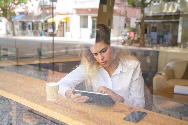 Koncentruje się kobiet zawodowych siedzi przy biurku w przestrzeni coworkingowej lub kawiarni, za pomocą tabletu