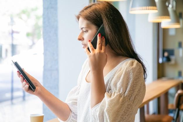 Koncentruje się kobieta rozmawia na komórce i patrząc na ekran tabletu