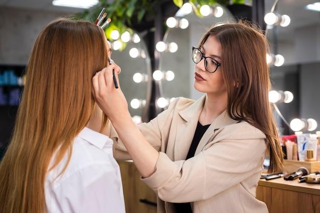 Koncentruje się makijażu artysta stosuje cień do powiek na kobiecie z muśnięciem