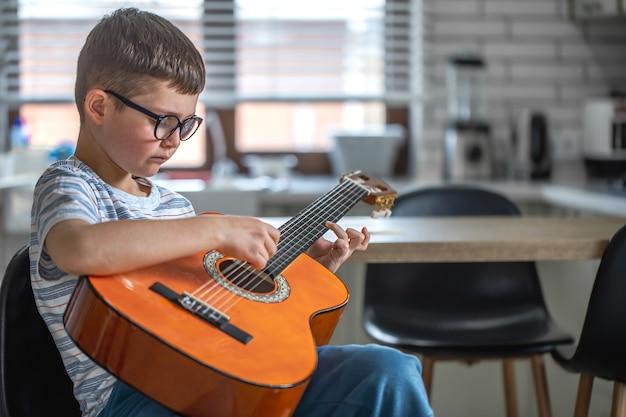 Koncentruje się mały chłopiec siedzi z gitarą w rękach w domu w kuchni.
