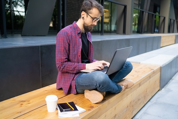 Koncentruje się mężczyzna siedzi ze skrzyżowanymi nogami na drewnianej ławce z laptopem