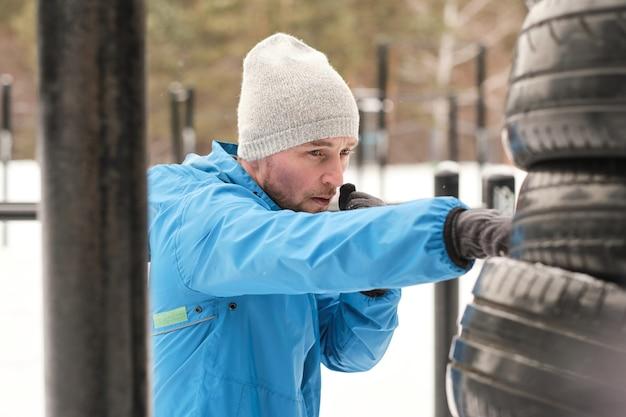Koncentruje się młody człowiek w kapeluszu i kurtce bokserski stos opon podczas treningu na świeżym powietrzu w zimie
