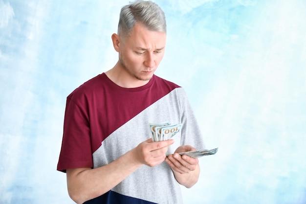 Koncentruje się młody człowiek z banknotów dolara na lekkiej przestrzeni