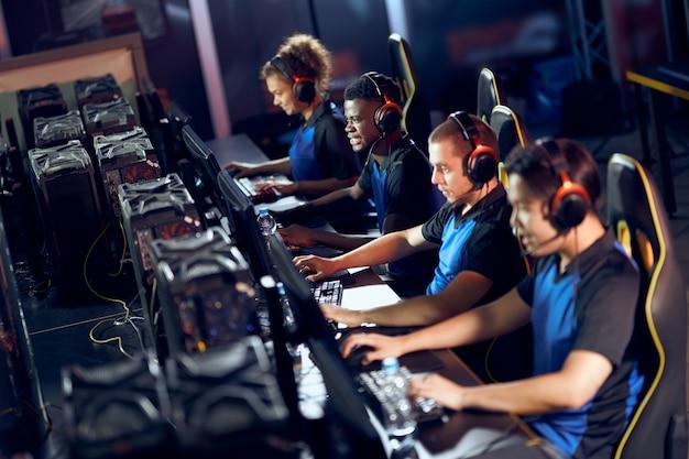 Koncentruje się na grze. zespół profesjonalnych graczy cybersportowych w słuchawkach biorących udział w turnieju esportowym podczas siedzenia w klubie gier lub kafejce internetowej