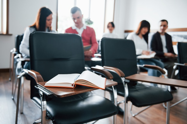 Koncentruje się na książce. grupa ludzi na konferencji biznesowej w nowoczesnej klasie w ciągu dnia