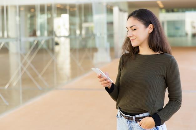 Koncentruje się pozytywna piękna kobieta ogląda zawartość na telefonie komórkowym