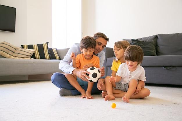 Koncentruje się tata trzyma piłkę i rozmawia z dziećmi. kochający kaukaski ojciec i dzieci siedzą na dywanie w salonie i bawią się razem. koncepcja dzieciństwa, aktywności w grach i ojcostwa