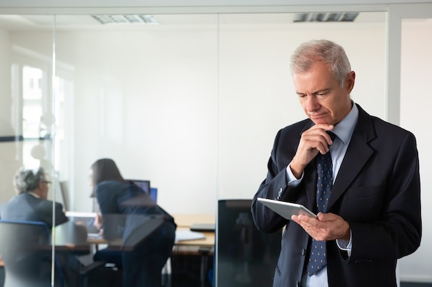 Koncentruje się zamyślony biznesmen wpatrzony w ekran tabletu, podczas gdy jego koledzy omawiają projekt w miejscu pracy za szklaną ścianą. skopiuj miejsce. koncepcja komunikacji