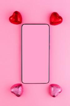 Koncepcja 14 lutego lub walentynki. w pobliżu smartfona leżą czekoladowe cukierki w czerwonych i różowych opakowaniach. makieta.