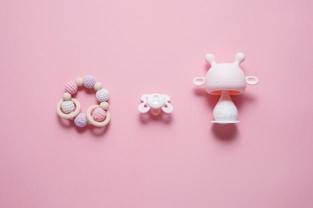 Koncepcja akcesoriów dla niemowląt: gryzak, zabawka gąsienica i smoczek dla niemowląt, na różowym tle z przestrzenią do kopiowania, widok z góry, leżak płaski