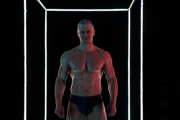 Koncepcja aktywnego stylu życia. profesjonalny kulturysta pokazujący doskonale umięśnioną sylwetkę, oświetlenie lampami w tle
