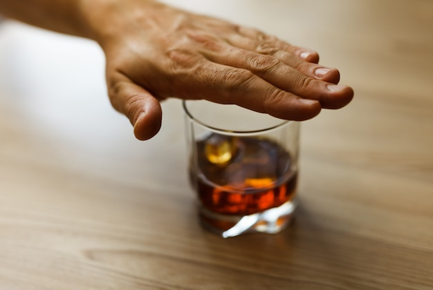 Koncepcja alkoholizmu. łańcuch whisky blokuje ręce