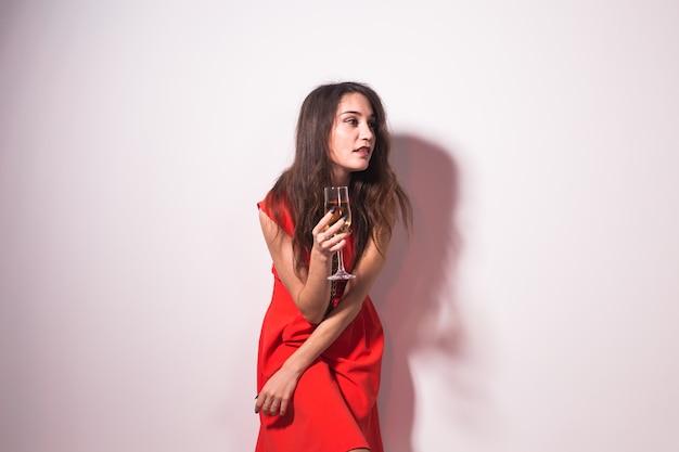Koncepcja alkoholu, wakacji i imprez - kobieta w czerwonej sukni z kieliszkiem szampana lub wina na białym tle