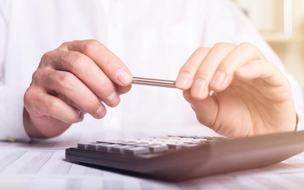 Koncepcja analizy finansowej, męskie ręce trzymając pióro i używając kalkulatora nad dokumentami księgowymi.