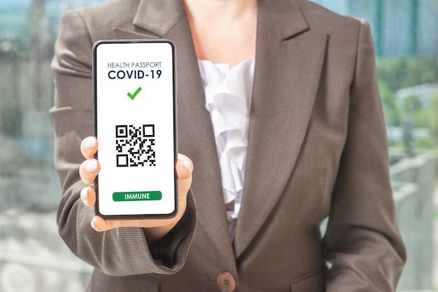Koncepcja aplikacji health pass covid19 na smartfonie. kobieta hodling telefon. kobieta trzyma inteligentny telefon z kodem qr
