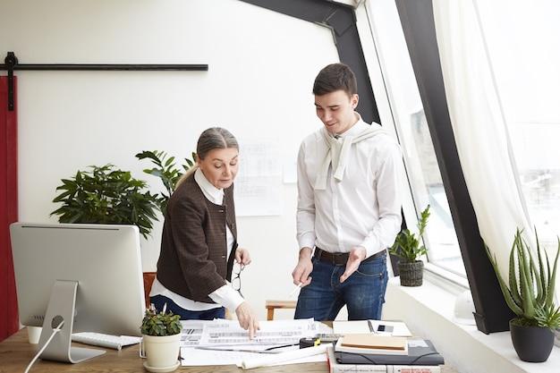 Koncepcja architektury, inżynierii i projektowania. zdjęcie szczęśliwego architekta brunetka mężczyzna uśmiecha się, podczas gdy jego doświadczona starsza koleżanka pomaga mu w jego projekcie budowlanym, zmieniając rysunki
