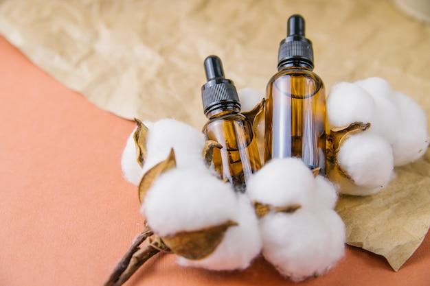 Koncepcja aromaterapii z butelką olejku eterycznego, kwiaty bawełny. kompozycja martwej natury do spa lub ziołolecznictwa.olejek kosmetyczny do pielęgnacji skóry i włosów.