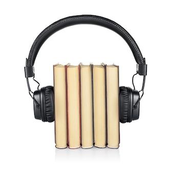 Koncepcja audiobooka. stos książek i słuchawek na białym tle