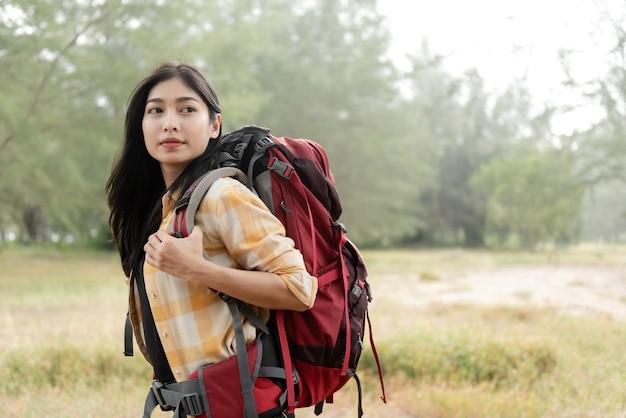 Koncepcja backpacker i piękna azjatka patrząc z ukosa, niosąc dużą czerwoną torbę idąc przez las na wędrówki.