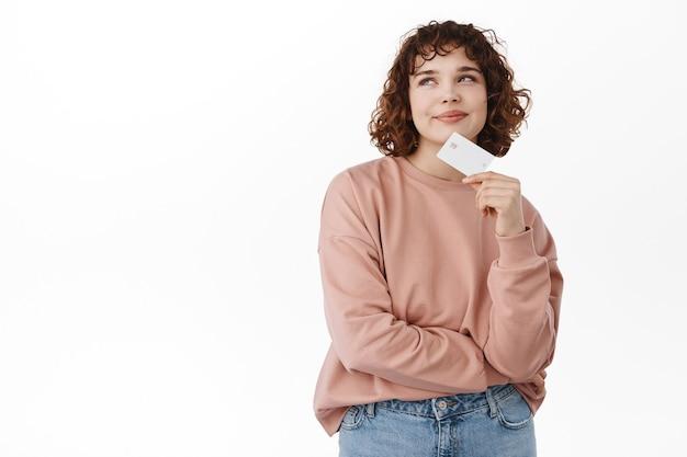 Koncepcja banku i finansów. zamyślona dziewczyna z kręconymi włosami trzymająca kartę kredytową, myśląca i patrząca w lewy górny róg, marząca o zakupach, zamierzająca coś kupić, stojąca na białym
