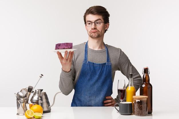 Koncepcja barista, pracownik kawiarni i barman. portret młodego męskiego pracownika gotującego deser, patrzejący tort na talerzu z sceptycznym niepewnym wyrażeniem, stoi baru kontuar