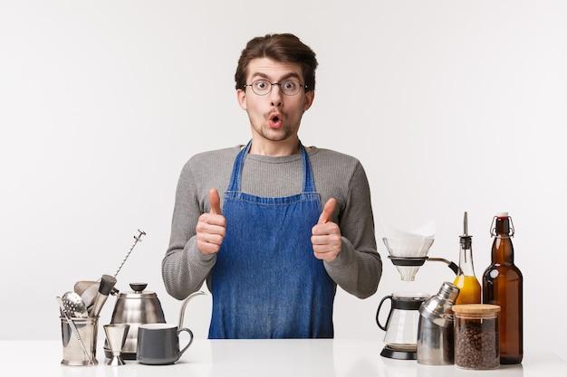 Koncepcja barista, pracownik kawiarni i barman. portret podekscytowanego i zafascynowanego młodego mężczyzny w fartuchu stojącego obok lady baru, pokaż kciuk pod wrażeniem, zatwierdź dobry smak kawy