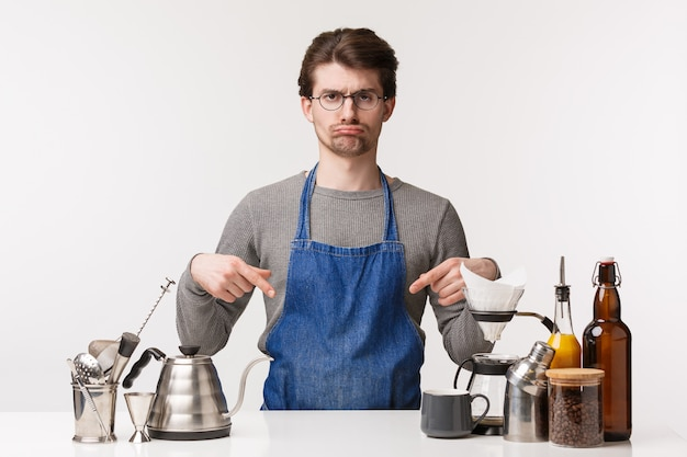 Koncepcja barista, pracownik kawiarni i barman. portret ponurego i zdenerwowanego ślicznego młodego pracownika płci męskiej pracującego w kawiarni uczy się jak robić kawę, wskazując na ladę barową i dąsać się niezadowolony