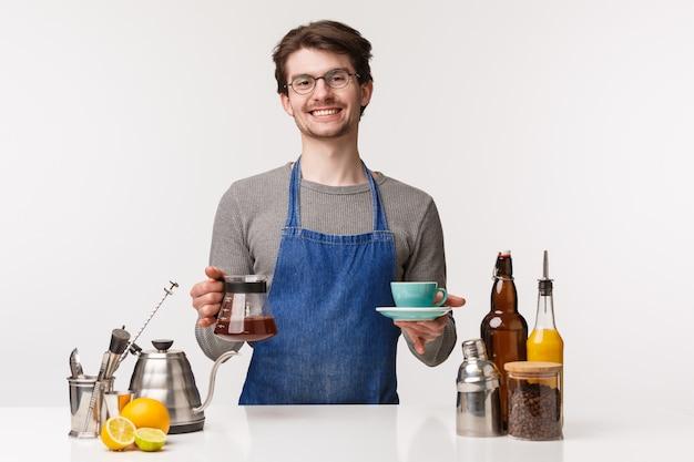 Koncepcja barista, pracownik kawiarni i barman. portret przyjazny miły uśmiechnięty mężczyzna w fartuchu daje klientowi filiżankę parzonej kawy filtrującej, trzymając napój i czajnik, na białej ścianie