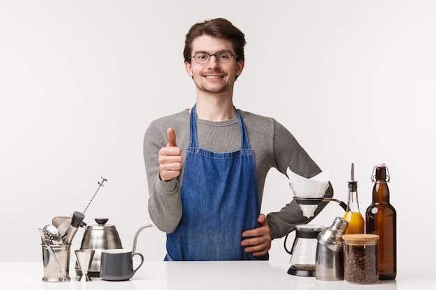 Koncepcja barista, pracownik kawiarni i barman. portret zadowolonego przystojnego młodego pracownika w fartuchu, pokaż znak kciuka i uśmiechnięty pewny siebie, gwarantuje, że spodoba ci się kawa, zatwierdzi