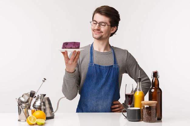 Koncepcja barista, pracownik kawiarni i barman. portret zadowolony uśmiechnięty, szczęśliwy młody męski właściciel małej firmy trzyma kawałek ciasta na talerzu z zadowolonym uśmiechem, stoi w pobliżu kontuaru baru