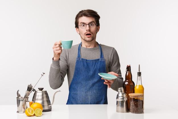 Koncepcja barista, pracownik kawiarni i barman. portret zdezorientowanego i niezdecydowanego młodego zszokowanego faceta w fartuchu wygląda na zaniepokojonego, gdy klient oddał kawę ze skargą, stojak z filiżanką