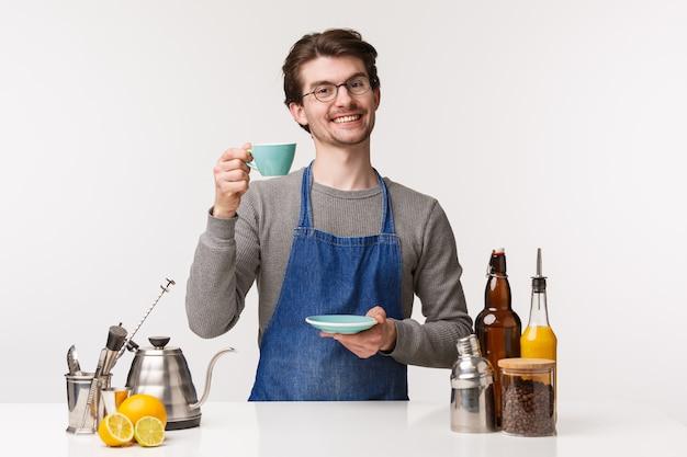 Koncepcja barista, pracownik kawiarni i barman. portret życzliwy młody uśmiechnięty męski pracownik pracuje w sklep z kawą mówić otuchy jak podnosi filiżankę herbata i uśmiecha się szeroko, biel ściana