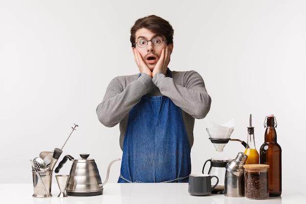 Koncepcja barista, pracownik kawiarni i barman. zszokowany, bezmowny młody kaukaski facet w fartuchu, wpatrujący się w zszokowane spojrzenie, w jaki sposób klient źle pije kawę, stojący obok baru z chemex