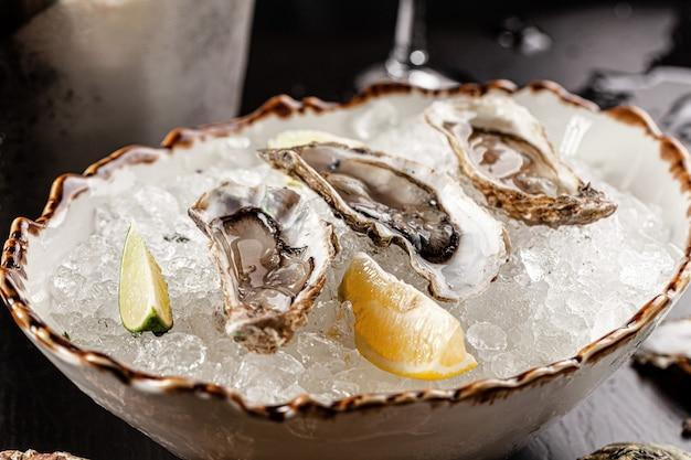 Koncepcja baru prosecco. otwarte ostrygi leżą na kruszonym lodzie z cytryną i limonką, obok kieliszka szampana. zdjęcie w tle. skopiuj miejsce.
