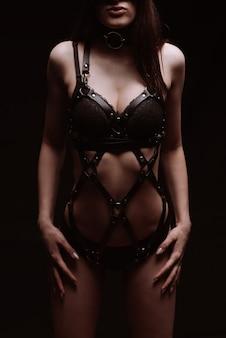 Koncepcja bdsm. seksowna dziewczyna w czarnej skórzanej bieliźnie.