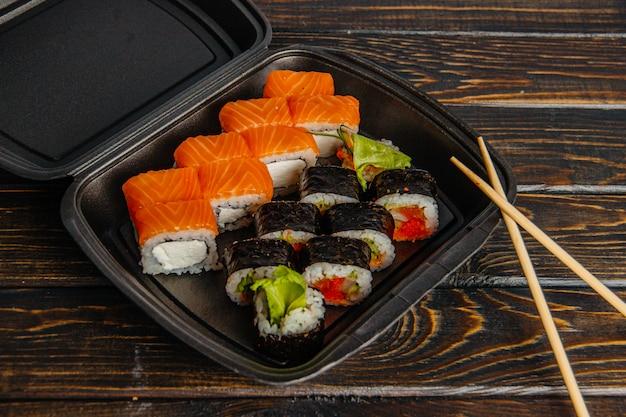 Koncepcja bezkontaktowej dostawy rolek sushi. czarne opakowanie z różnymi rolkami i pakiet rzemiosła na drewnianym stole.