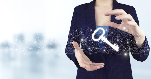 Koncepcja bezpieczeństwa i ochrony. dwie ręce trzymając wirtualny klucz holograficzny ikona z jasnym niewyraźnym tłem. pojęcie prywatności ochrony danych. rodo. ue.