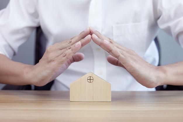 Koncepcja bezpieczeństwa w domu chroniąca gest mężczyzny i modelu domu
